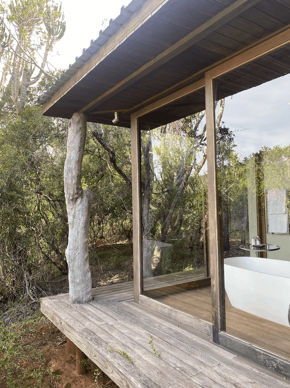 Outdoor View of Bathroom with large windows surrounded by trees